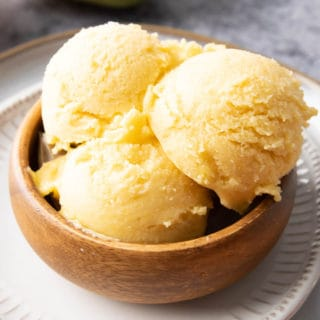 Homemade Mango Ice Cream: this 3 ingredient mango ice cream recipe is super EASY! 5 mins of prep for the best mango ice cream: rich & creamy with big mango flavor! Vegan, Dairy-Free, Healthy #Mango #IceCream #Vegan #DairyFree | Recipe at BeamingBaker.com