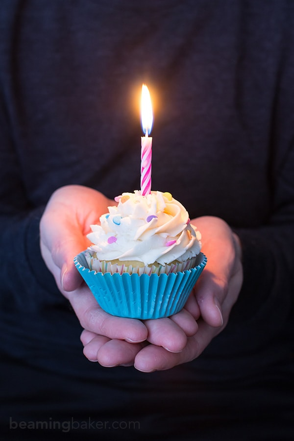 cupcake with lit candle in cupped hands