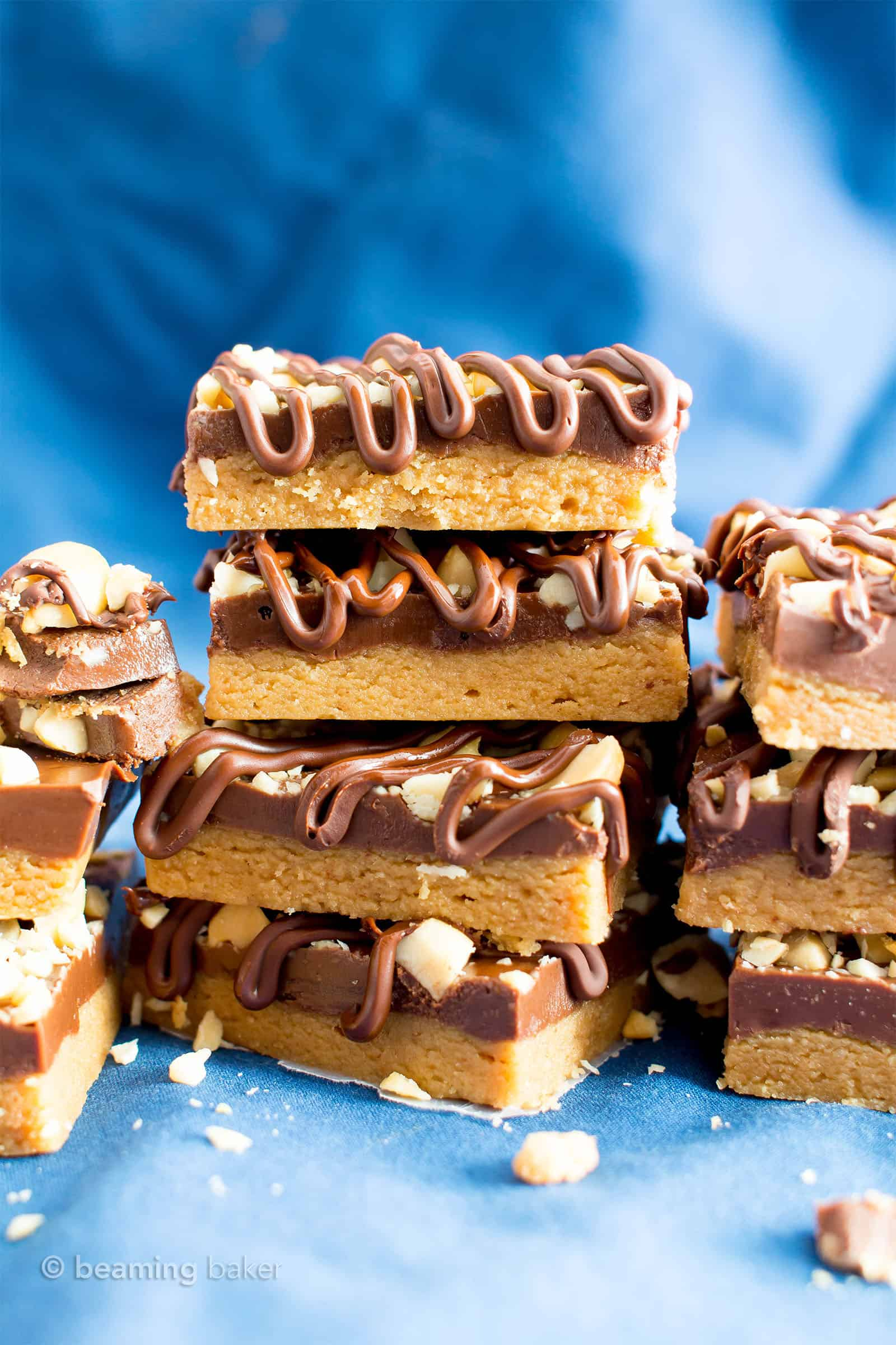 No Bake Peanut Butter Bars (Healthy): the ultimate healthy no bake peanut butter bars—just 5 ingredients, with thick layers of chocolate & peanut butter, a crunchy topping & velvety chocolate drizzle. #PeanutButterBars #Healthy #NoBake #Chocolate #PeanutButter | Recipe at BeamingBaker.com